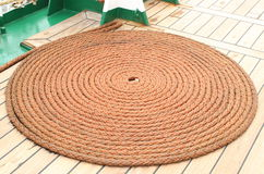 Thick rope wrapped in spiral lying on deck of ship Royalty Free Stock Image