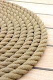 Thick rope wrapped in spiral lying on deck of ship Stock Image