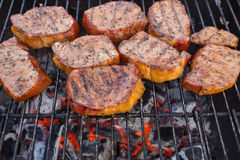 Thick seasoned pork chops cooking on the grill Royalty Free Stock Photos