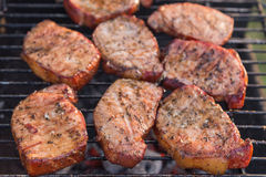 Thick seasoned pork chops cooking on the grill Royalty Free Stock Images