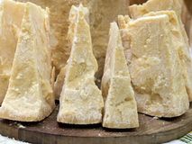 Thick slices of Italian Parmesan cheese on a wooden cutting boar Stock Image