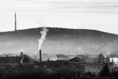 Thick smog layer above town, smoking chimney, hills on top stock image