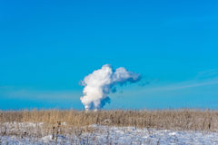 Thick smoke against the blue sky. Thick smoke coming out of high pipes on the background of blue sky stock photo