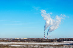 Thick smoke against the blue sky. Thick smoke coming out of high pipes on the background of blue sky Royalty Free Stock Photo