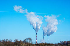Thick smoke against the blue sky. Thick smoke coming out of high pipes on the background of blue sky Stock Photos