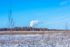 Thick smoke against the blue sky. Royalty Free Stock Images