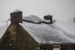 Roof exposed after snow slid off circa 1800 building. Thick snow on house roof has slid off leaving exposed slate roof tiles and broken edges of the remaining Royalty Free Stock Photo