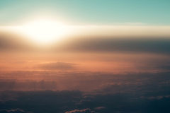 Thick soft clouds in hazy rosy air on idyllic sky. Celestial sphere, illuminated by sun light on blurred overcast background. Upper layers of atmosphere stock photography