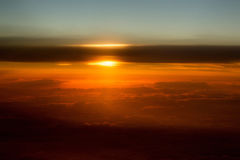 Thick soft clouds on idyllic grey sky. Celestial sphere, in slanting rays of setting sun on orange overcast background. Upper layers of atmosphere Royalty Free Stock Photo