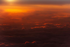 Thick soft clouds on idyllic sky. Celestial sphere, in slanting rays of setting sun on orange overcast background. Upper layers of atmosphere Royalty Free Stock Photo