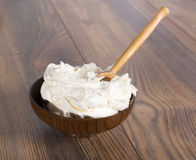 Thick sour cream in a bowl and wooden spoon Royalty Free Stock Image