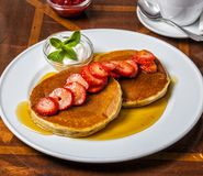 American pancakes with warm maple syrup, strawberries and cream stock photo