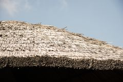 Thick straw thatched roof. Traditional architecture construction Stock Photos