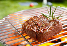 Steak on a grill. A thick strip steak being grilled outdoors Royalty Free Stock Photography