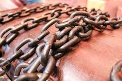Strong, iron, old chains against the background of a wooden brown trunk. Stock Photos