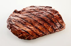 Thick succulent portion of barbecued flank steak. Grilled in a spicy marinade viewed uncut over white at a high angle royalty free stock images