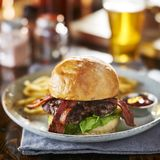 Thick tasty bacon cheese burger on brioche bun served with fries on plate. Shot with selective focus stock photography