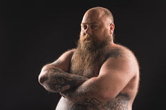 Thick tattooed guy expressing seriousness. Waist up portrait of serious fat naked bearded man standing with crossed arms. He has tattoo over all his body Stock Photo