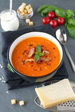 Thick tomato soup with basil and fried bacon in a black ceramic bowl on a grey abstract background. Healthy eating Royalty Free Stock Photography