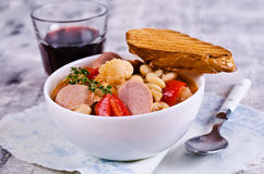 Thick vegetable soup. With beans and sausages. Selective focus royalty free stock photography