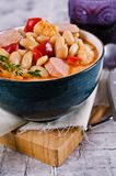 Thick vegetable soup. With beans and sausages. Selective focus royalty free stock image