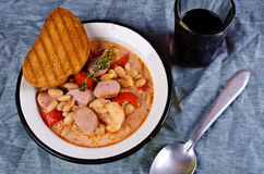 Thick vegetable soup. With beans and sausages. Selective focus royalty free stock photo
