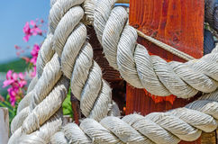 Thick white rope. Mooring rope around a wooden jetty bollard Royalty Free Stock Photos