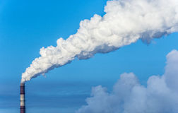 Thick white smoke from the chimney. Thick white smoke from the chimney on the background of dark blue sky royalty free stock photography