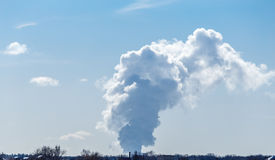 Thick white smoke from the nuclear plant in the distance against the bright blue Stock Photo