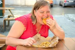 Free Thick Woman Eating Fast Food Hamburger And French Fries In A Caf Royalty Free Stock Photos - 104969668