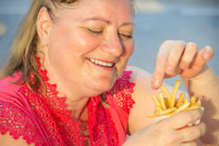 Thick woman eating fast food hamburger and french fries in a caf Royalty Free Stock Images