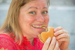 Thick woman eating fast food hamburger and french fries in a caf Stock Photography