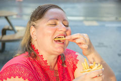 Thick woman eating fast food hamburger and french fries in a caf Royalty Free Stock Image