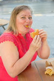 Thick woman eating fast food hamburger and french fries in a caf Stock Photos
