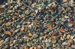 Through the thickness of the transparent water. You can see the bottom consisting of pebbles, stones, sand. Background of a round stone pebbles on the bottom of Stock Image