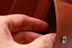 Thief. Hand stealing from leather wallet Stock Photos
