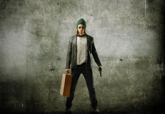 Thief. Young thief holding a gun and a suitcase stock photography
