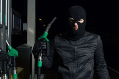 Thief. Masked man using gas pump Royalty Free Stock Images