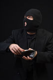 Thief. A thief wearing a balaclava snooping through a wallet, shot against a dark background Stock Images
