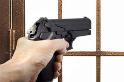 Thief armed with a pistol. In front of a gate royalty free stock photos