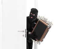 Thief with a bag full of money entering a room Stock Photography