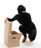 Thief in balaclava with boxes Stock Photo