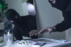 Thief in balaclava. Breaking into the house Stock Image