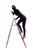 Thief in balaclava entering on ladder Royalty Free Stock Photography