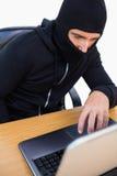 Thief with balaclava hacking a laptop Stock Photos
