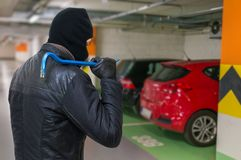Thief in balaclava holds crowbar in hand and is going to steal a car. Stock Image
