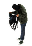 Thief in  balaclava with stolen backpack Stock Image