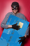 Thief with big blue credit card. Thief holding big blue credit card and ironic smiling Stock Image