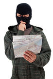 Thief in black balaclava with map Royalty Free Stock Photos
