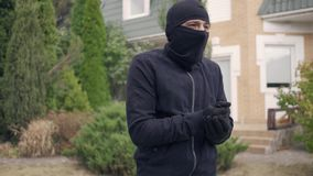 Thief in black clothes and balaclava before breaking into house. The guy going to steal things in rich house. Concept of. Offense against the law, robbery stock video footage